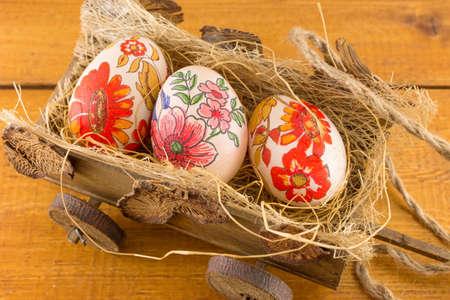 carreta madera: Decoupage decorado huevos de Pascua en un antiguo vagón de madera Foto de archivo