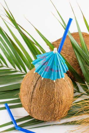 cocktail umbrella: Fresh coconut cocktails with cocktail umbrella placed on coconut leaves Stock Photo