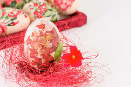 decoupage: Decoupage decorated Easter egg on red straw Stock Photo