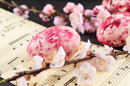 sheet music: Decorated Easter eggs and fresh cherry blossom tree on sheet lines