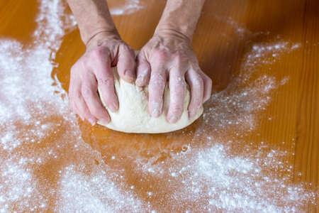 haciendo pan: Manos de un macho toma de panadero pan en la mesa Foto de archivo