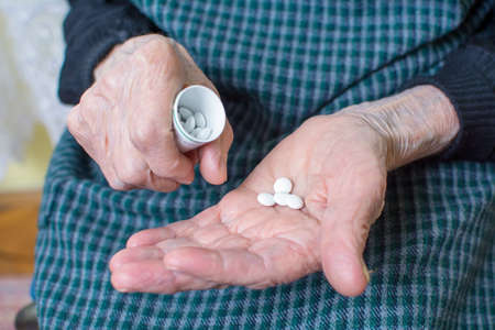 80 90: Hands of very old woman taking pills