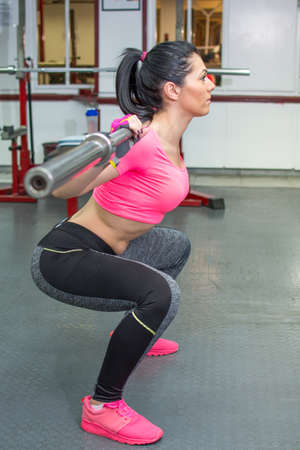 squats: Girl doing squats with a bar at the gym Stock Photo
