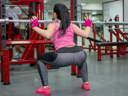 knees bent: Girl doing squats with a bar at the gym Stock Photo