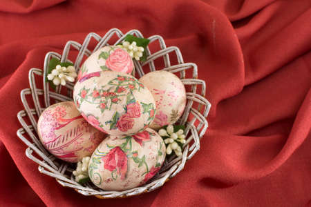 sof: Colorful decoupage decorated Easter eggs in a basket with sof red background Stock Photo