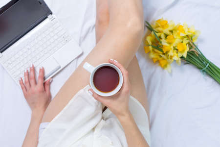 Woman having a morning cup of tea in bed