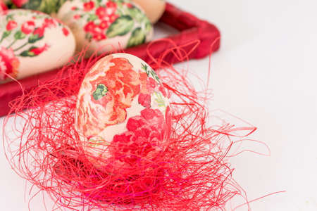 red straw: Decoupage decorated Easter egg on red straw Stock Photo