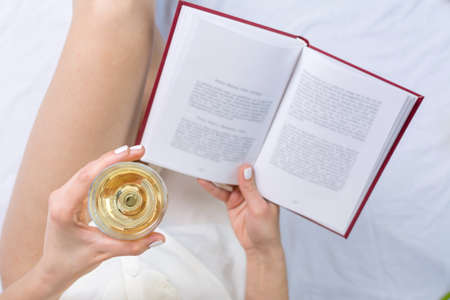 Woman having a glass of white wine in bed 스톡 콘텐츠