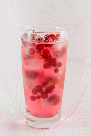 berry: Berry fruit juice with ice cubes against soft pink background