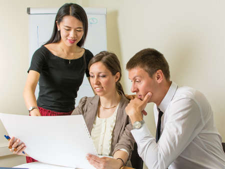 Multicultural team of designers looking at a project at work