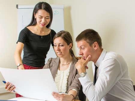 reuniones empresariales: equipo multicultural de dise�adores mirando un proyecto en el trabajo