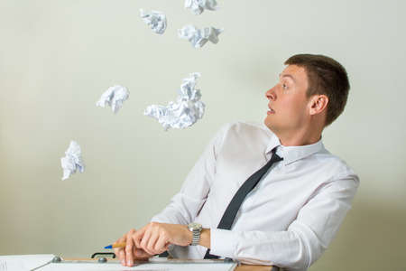 paper sheets: Crumpled papers flying into young businessman face