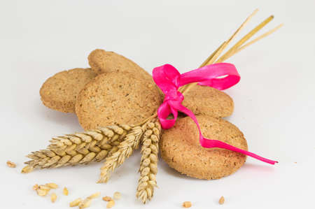 integral: Integral cookies and a decprated wheat plant on white baclground Stock Photo