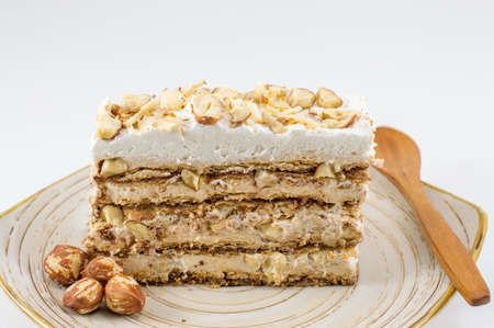 Hazelnut cake slice on a plate aginst white background Standard-Bild