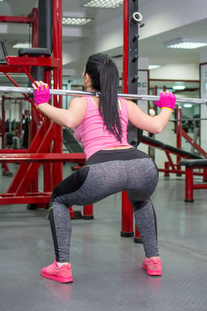 Girl doing squats with a bar at the gym Stock Photo