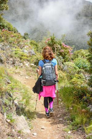 descending: female mountaineer descending down a trail