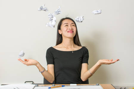 asian architect: Happy asian woman throwing crumpled  papers at work