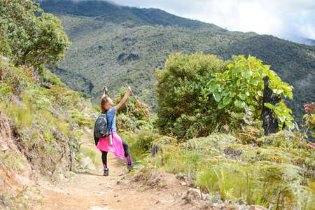 raising hands: female raising hands on a trail in the mountains