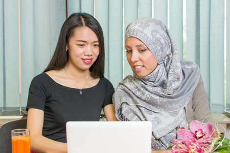 Asian and muslim girls working together on a laptop Reklamní fotografie