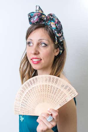 Giovane donna in costume da bagno in possesso di un ventilatore della mano