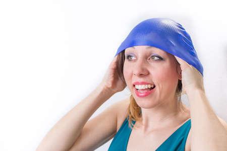 personas banandose: Feliz niña ajusta su sombrero de la natación en un traje de baño
