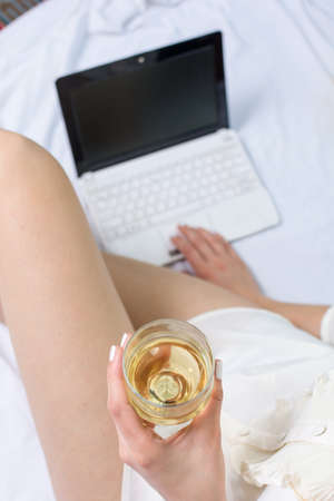 glass bed: Woman having a glass of white wine in bed Stock Photo