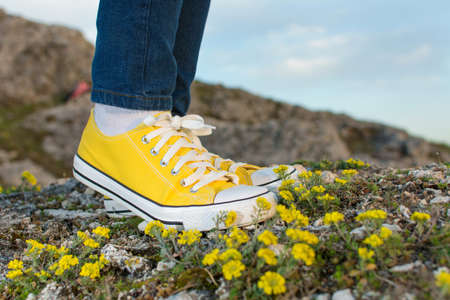 no face: Woman on a hiking trip with close up at yellow sneakers
