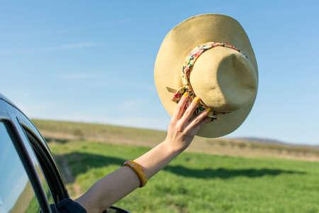 thru: Woman hand with a hat thru car window. Travel time