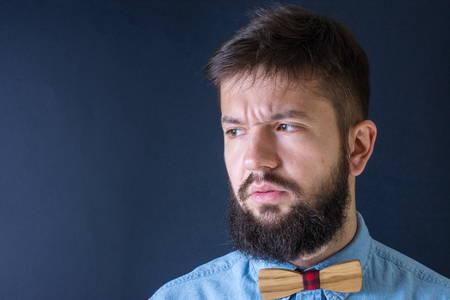 hombre con barba: hombre de la barba enojado en una camisa azul Foto de archivo