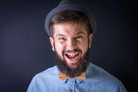 hombre con barba: Yealing enojado hombre de la barba en una camisa azul Foto de archivo