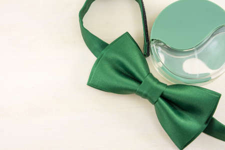 parfume: Green Bow tie and parfume  on a wooden table