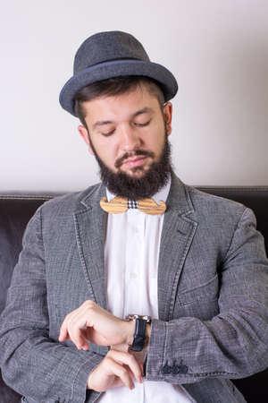 hombre con barba: hombre de la barba en un juego que lleva un tiempo cheking pajarita Foto de archivo