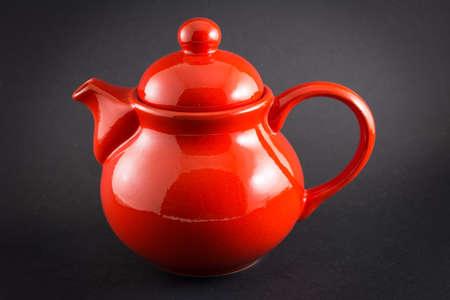 shiny black: Read shiny teapot on black background Stock Photo