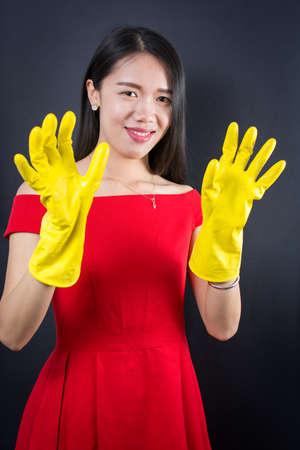 Geklede omhoog Aziatische vrouw, gekleed in gele schoonmaak handschoenen Stockfoto