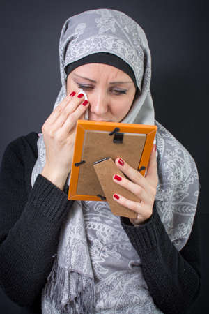old photograph: Muslim woman moaning over an old photograph in a frame