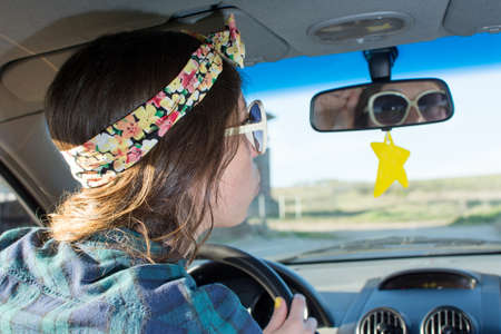 cliche: Young woman driving a car and looking herself at the mirror