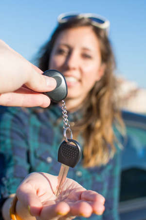 handed: Let you be the driver. Young female being handed the car keys Stock Photo
