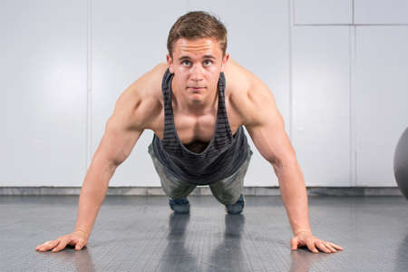 muscle gain: Young man performing push ups at the gym