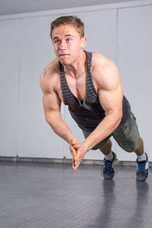 muscle gain: Man performing push ups with applause at the gym