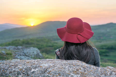 Female hiker enjoying sunset while sitting on a rock Stock Photo