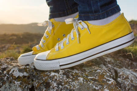low angle views: Woman on a hiking trip with close up at yellow sneakers