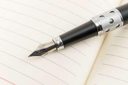 open notebook: Black fountain pen on a open  notebook Stock Photo