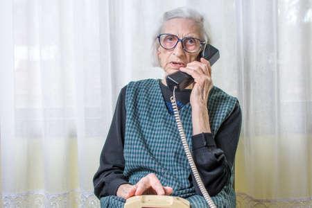 실내 휴대 전화를 사용하는 90 세 여성 여성 스톡 콘텐츠