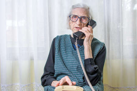 90 years old woman woman using the phone indoors