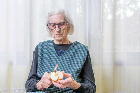 ninety: Ninety years old grandma slicing and peeling an apple indoors