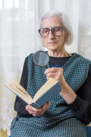 80 90: Ninety years old grandma reading a book through magnifying glass Stock Photo