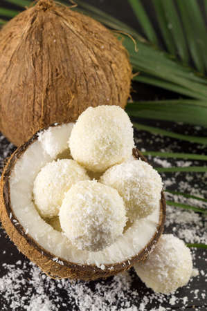 half ball: Fresh coconut and coconut cookies on dark wooden background