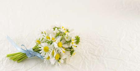 Chamomile bouquet on white textile