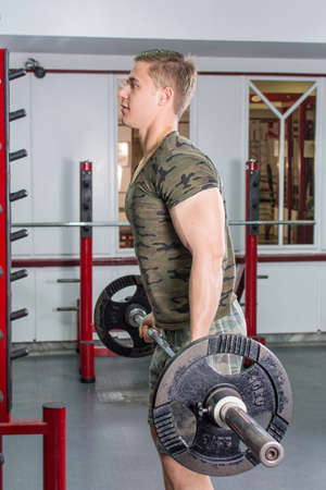 muscle gain: Man performing barbell curl at the gym. Biceps workout