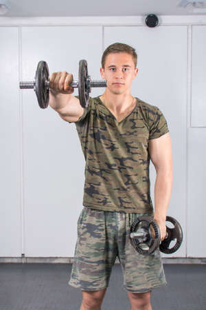 muscle gain: Man performing shoulders workout at the gym Stock Photo